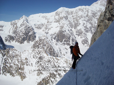 A traverse on Mount Huntington's Colton-Leach route. Denali's south buttress is visible in the background.