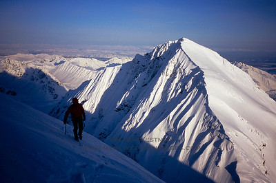 Eamonn Walsh approaches the summit of Mount Grosvenor after making the first ascent of the mountain's 4,400 foot tall east face. Mount Church is to the mountain on the right.