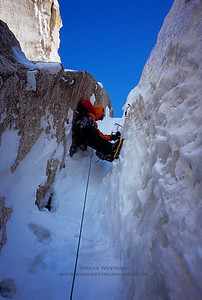 Eamonn Walsh chimneys past a snow-choked slot during the first ascent of the east face of Broken Tooth.