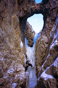 Climbing through the natural arch, Super Bock, Yoho National Park, British Columbia.