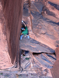 Climber leading the second pitch of Lonely Vigil on Lighthouse Tower, near Moab, Utah.