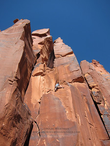 Tom Dancs leading the first pitch of Thunderbolts on the east face of Easter Island Tower, Indian Creek, Utah.