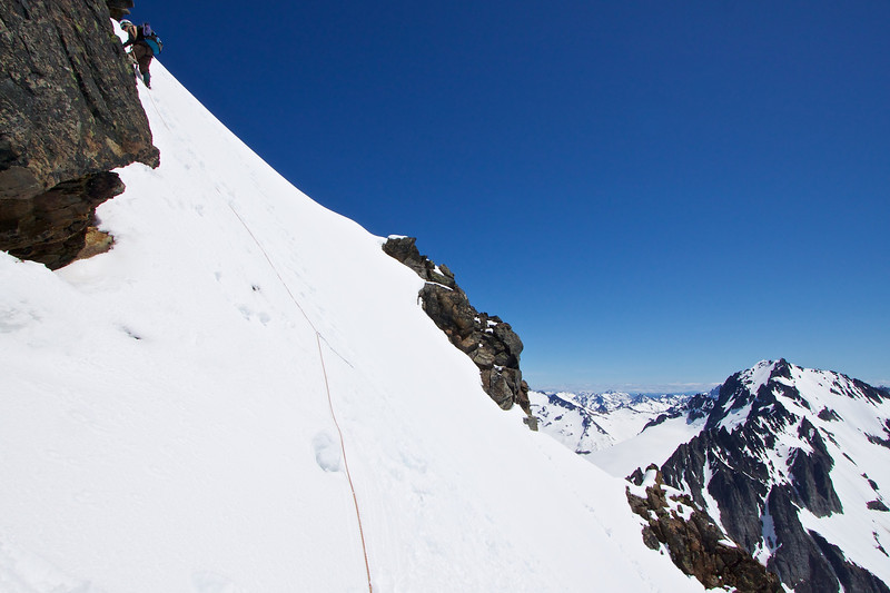 Around the backside of Sahale.  This was a sketchy slope, IMO.  I was very careful not to post-hole more than 1 foot.  The pickets were more cosmetic than effective.  In 20 more feet Monique hits rock and with no rack, we turn around, 15 feet from the summit.  Oh well!<br /> Buckner in background.