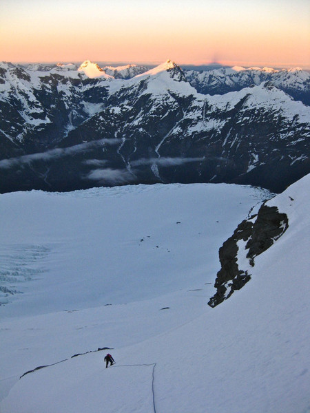 Mt Aspiring's shadow extends over the glacier below and across the peaks over the valley.