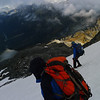 Descending a glacier to the ridge leading back to Brodrick Pass in the sun below.