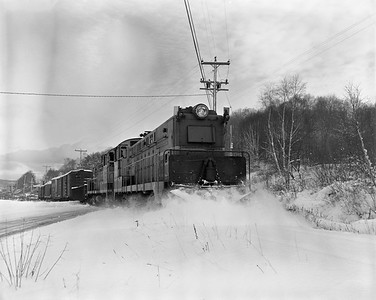 2021.008.4.047A--clint jones 4x5 neg--COPR--BLW diesel locomotive 100 and 101 on southbound freight train plowing snow Coles Creek crossing leaving--Houghton MI--no date
