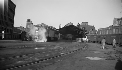 2021.008.1.018--clint jones 116 neg--CMStP&P--FM diesel locomotive 9A on passenger train 24 arrival at depot--Milwaukee WI--c1960 0000. Train 12 for Watertown is seen in background inside trainshed.