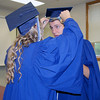 SHERRY VAN ARSDALL | THE GOSHEN NEWS<br /> Senior Hallie Wingard cuts pieces of thread from the cap of senior Benson Yoder before the commencement ceremony at Clinton Christian School in Goshen Friday evening.