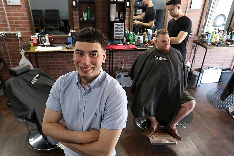 "Owner of Clippers & Co. Caleb Rivera in his shop as Geno Neagle gets his hair cut for the second time by Brian Martinez on Wednesday afternoon. When neagle was asked what he thought of the new barber shop he said "" I Love It."" SENTINEL & ENTERPRISE/JOHN LOVE"