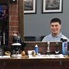Caleb Rivera owner of Clippers & Co. in Leominster can be seen in one of the mirrors in the new Barber shop. SENTINEL & ENTERPRISE/JOHN LOVE