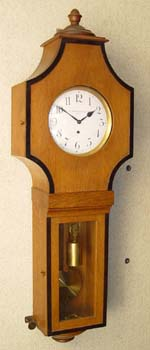 Clock No. 371<br /> Claterbos lists a pair of gentlemen, probably brothers, who could have made this clock. Firstly, Franz, who qualified as a clockmaker in 1816. Then Alois, who is listed in 1863, a second Franz, who qualified in 1883, a Friedrich who qualified in 1881, a Leopold, who was producing clocks from roughly 1828 to 1852, and a Rudolf, who was prize winning clock-maker in 1905. It begins to sound like we are seeing the product of a third generation Viennese clockmaker, probably either Franz (jr), or Friedrich. None the less, I would date this clock in the period right around 1900. <br /> <br /> The case style reflects the European shift away from the classical styles of furniture, towards the experimentation that was rampant in during the closing years of the 1800's and into the first quarter of the 1900's. Jugendstil, Art Nouveau, Art Modern, and, a bit later, Deco: In the US we saw the emergence of the Arts and Crafts style – Let England drown in the massive Edwardian style - France, Germany, Austria and America were moving on, into a new, and visually stimulating world. <br /> <br /> When I first saw pictures of this clock I thought it was surely a large piece, measuring 50 or 60 inches in length. Imagine my surprise when I found it was a miniature, perfect in every detail. <br /> <br /> This clock is so very small, measuring just 32 inches from top to bottom, with every part scaled to match. Note the very small, zinc-backed bob (just 3.25 inches in diameter, and in perfect condition), the 5.5 inch dial, the 2.25 inch weight, the miniature pulley, a perfect fit, with the weight lines hanging parallel as they should, and, of course, the crowning element - the miniature mechanism, with its Graham dead-beat escapement, in clean, and running condition. It was interesting when I took the weight off to move this clock. It had been running, and, with the weight off, it just kept right on ticking. No, it does not have maintaining power, but clearly, the mechan