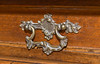 A lovely detail, the very ornate drawer pull for the drawer that is found between the base and the trunk of this clocks case