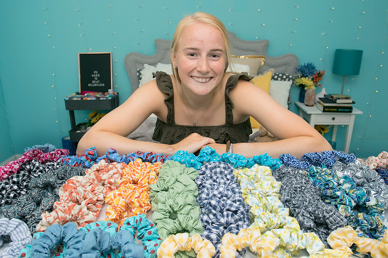 Chloe Dewhurst, 19, of Lancaster and a student at Springfield college has started a scrunchie business out of her bedroom. She calls her company BBE Scrunchies (Brave Bold Energy). Dewhurst shows off just some of the scrunchies she has ready for sale as she sits on her bed in her bedroom in Lancaster. SENTINEL & ENTERPRISE/JOHN LOVE
