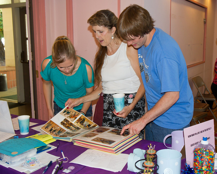 Kaylee, Michelle, and Ian looking at the NCCA book at Blossom Hill Festival, Aug. 2012.
