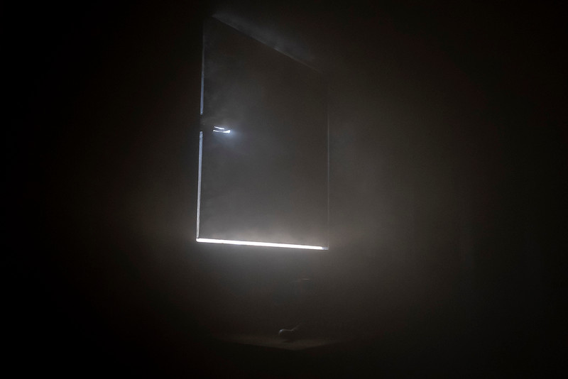 Light sneaks through the cracks of a make shift window in Estes Valley Fire's training facility during a live burn demonstration.
