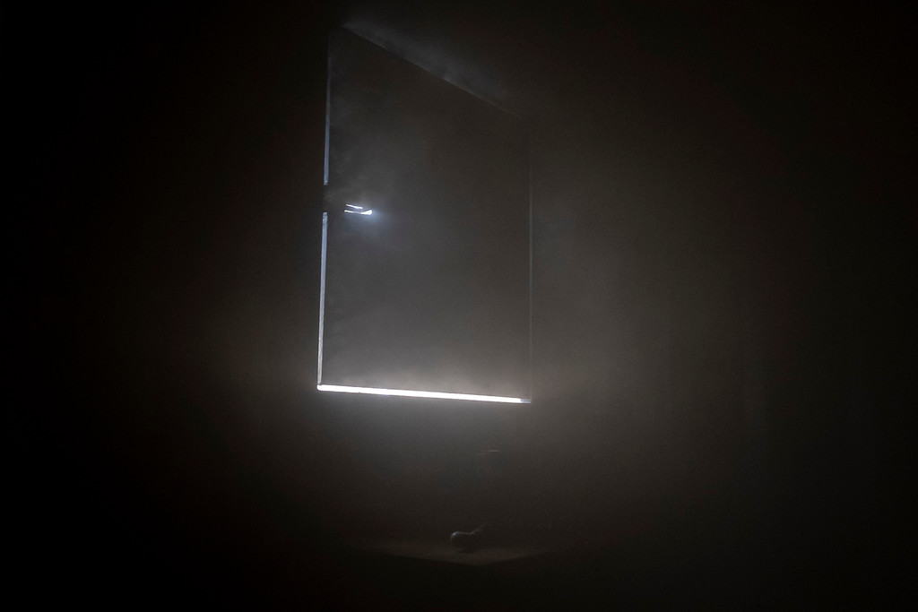. Light sneaks through the cracks of a make shift window in Estes Valley Fire�s training facility during a live burn demonstration.
