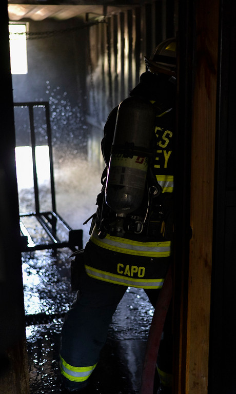 . Paul Capo with the Estes Valley Fire Protection District puts out a controlled fire as part of a live burn demonstration showing the efficacy of a closed bedroom door in the unlikely event of a home fire.
