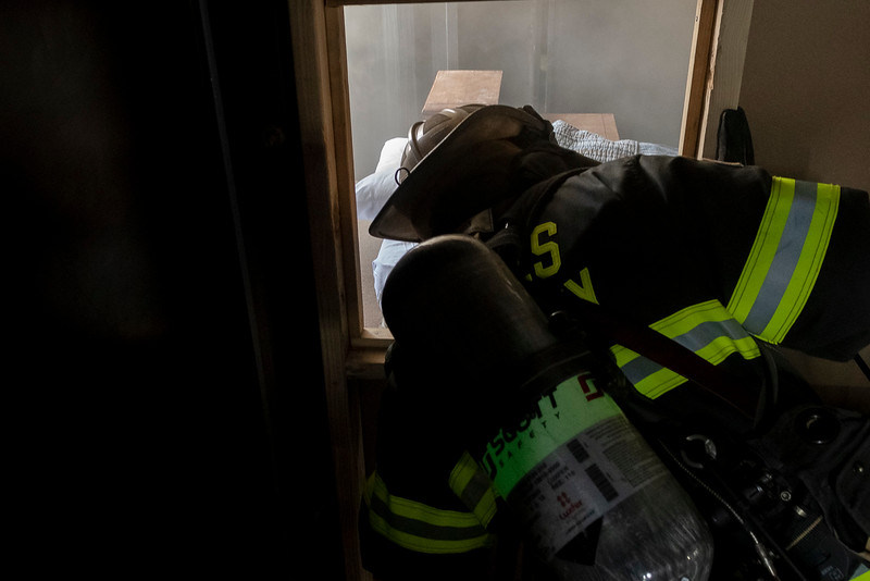 Chief David Wolf looks through the bedroom window at the blaze that's just down the hall.