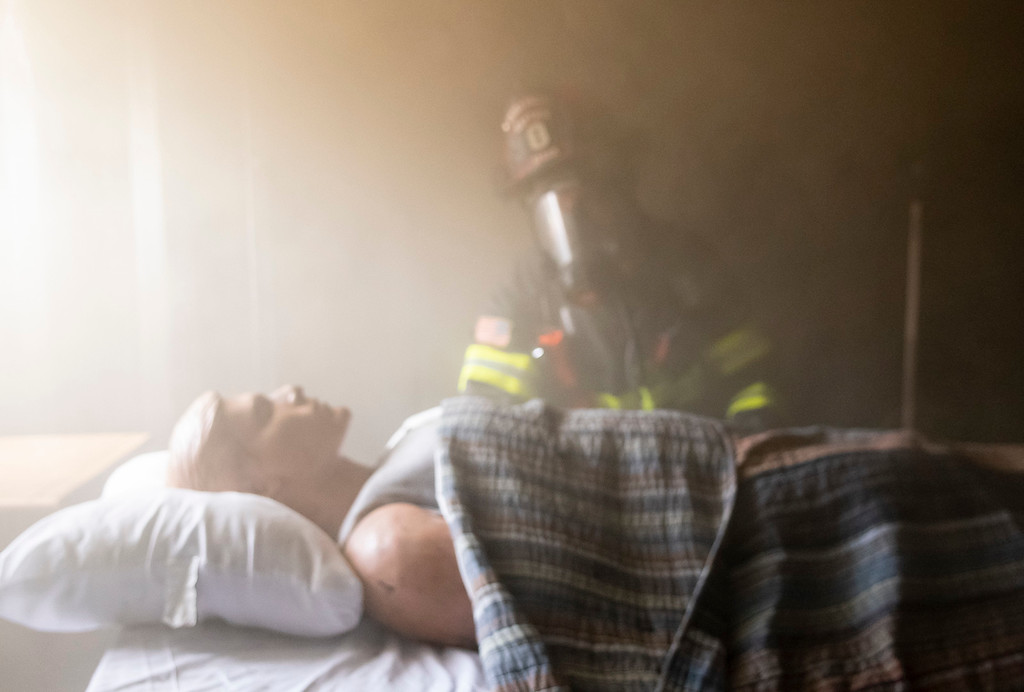 . A firefighter looks on to a human dummy who would be feeling some serious effects of carbon monoxide poisoning as a fire enters the bedroom where it is sleeping.