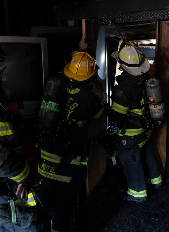. Fire crews forcefully remove the bedroom door prior to a second burn.