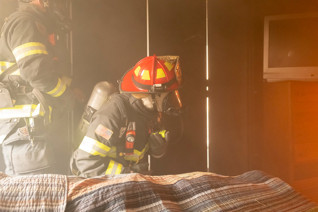 . Estes Valley firefighters await the fire to breach the doorway of the bedroom.