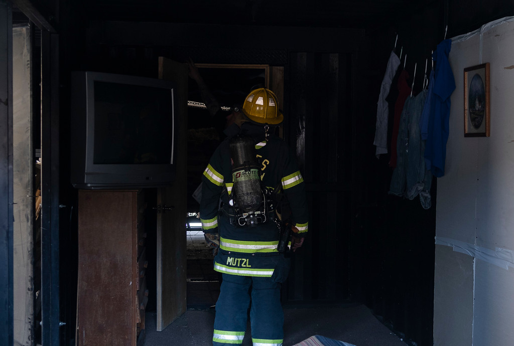 . Fire Inspector Nate Mutzl looks at the damage that the fire did on the other side of a closed bedroom door.