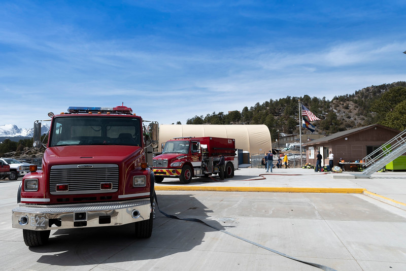 Outside Estes Valley Fire's training facility on Elm Road, firetrucks wait to put out a controlled blaze within the facility.