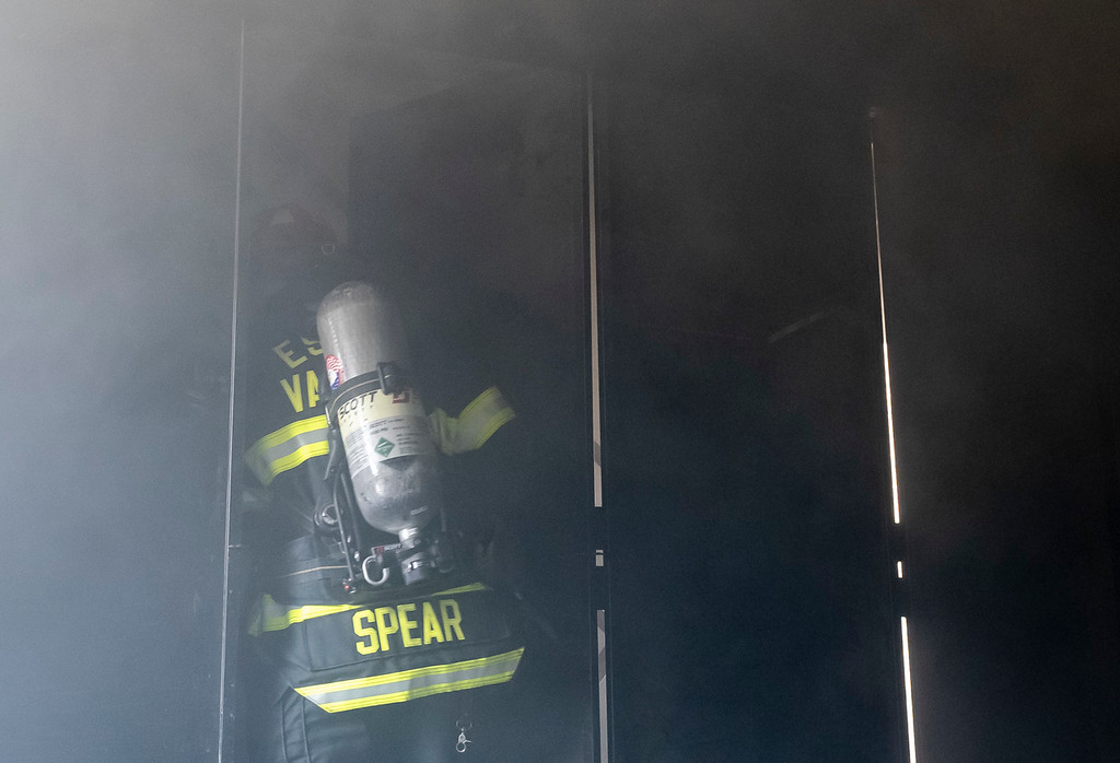 . Rick Spear breaches a doorway during a contolled house fire at the Estes Valley Fire training facility.