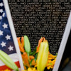 """Flowers left by loved ones in front of the names of fallen soldiers at Carter Park during the final day of """"The Wall That Heals"""" in Leominster on Saturday afternoon. SENTINEL & ENTERPRISE / Ashley Green"""