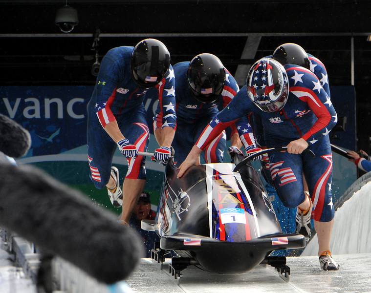 "OLY1014-TeamHolcombPush5028.jpg: Former U.S. Army World Class Athlete Program bobsledder Steven Holcomb (front right) leads ""The Night Train"" team of Justin Olsen, Steve Mesler and Curtis Tomasevicz to a start time of 4.77 seconds in the third heat of the Olympic four-man bobsled event. The quartet won an Olympic gold medal in bobsleigh for Team USA for the first time in 62 years at the Whistler Sliding Centre on Saturday. Photo by Tim Hipps, FMWRC Public Affairs"