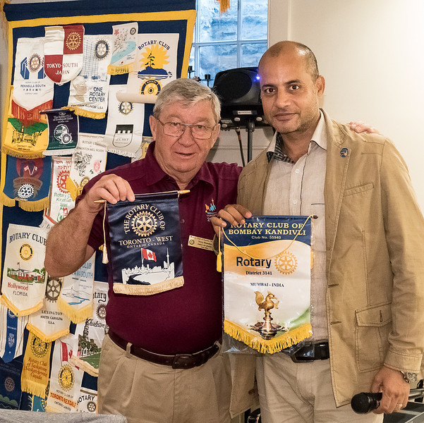 RTW President Terry Donohue  exchanges club banners with Sanjeeve Dutt, recently arrived from Mumbai India with his family.  San has adopted our club and hopes become a member very soon.