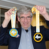 Hugh holds up two participation medals from recent Goal events…