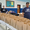 """Nutrition Manager Sally Thayer of Lowell and Sports & Fitness Manager Devonna """"D"""" Williams of Methuen fill bags with meals."""
