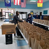 Staff member Becca and Pathways Manager Na Lam of Lowell fill bags.