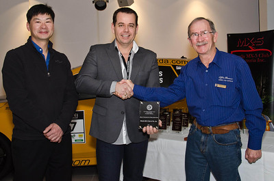 """Neil Choi (left), AROCA competition secretary and Ross Flood (right), AROCA president, present Daniel White (Club Captain - Motor Sport) with the Alfa Club's """"Most Supportive Organisation"""" award"""