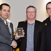 Tim Emery (centre) receives the Captain's award from Daniel White and Eugene Arocca