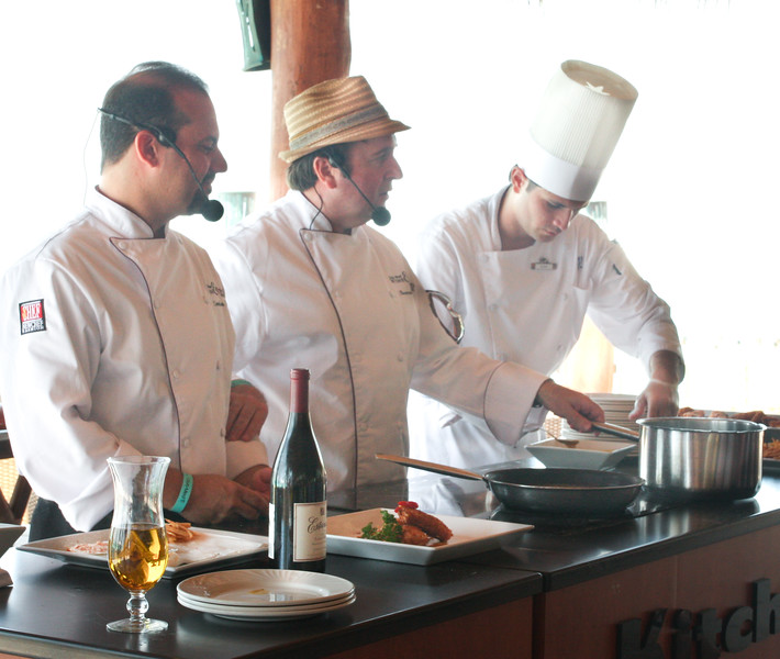 Chef Leandro Diaz (left), Chef Bernard Guillas (middle), and Club Med Chef Alex preparing Chef Diaz's Cashew Crusted Red Snapper with Yucca Fritter and Shrimp Saffron Sauce.