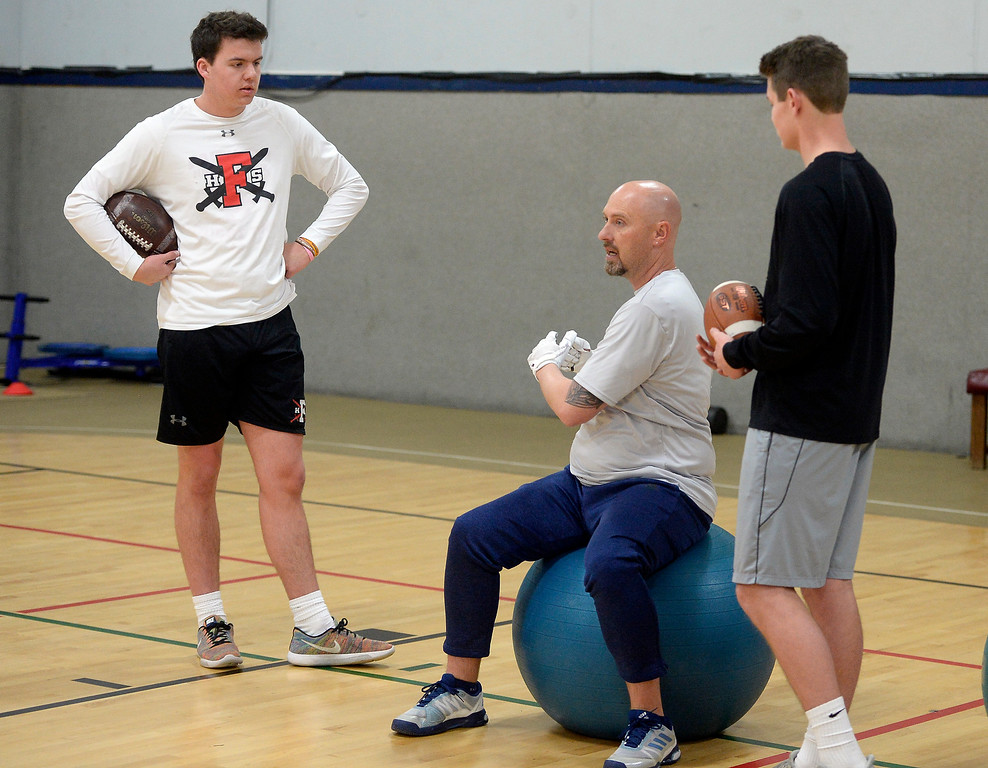 . LONGMONT, CO: February 16, 2019:  Warren McCarty demonstrates the next drill for Aiden Atchinson, left, and Chase Silva. Skyline quarterback Chase Silva and Fairview quarterback Aidan Atkinson met with coach Warren McCarty for a regular training session in Longmont. Warren McCarty has been a private football personal trainer and coach that has impacted the lives and athletic careers of dozens of the top players from the Boulder County area. He is a Longmont resident and specializes in quarterbacks (he was one), but also runs a recruiting business that is based on the relationships be built during his 10-year career in pro football, as well as representing collegiate and professional football coaches as an agent. (Photo by Cliff Grassmick/Staff Photographer)
