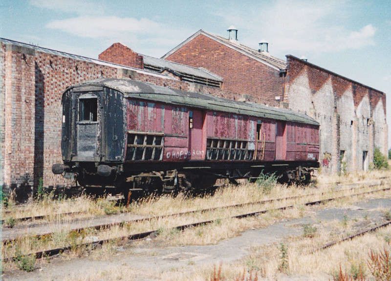 ADE320703 sits by the side of the derelict March steam shed on 29th July 1990
