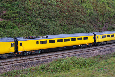 977993 - New Measurement Train Overhead Line Testing Coach (Converted from TGS 44053 and fitted with a Pantograph above the former guards compartment), now wearing unbranded Network Rail Yellow heads north into Dawlish Warren passing Langstone Rock 26/08/11