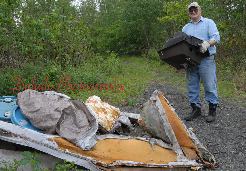 Jim Koharski, president of the Shamokin Creek Restoration Alliance (SCRA), prepares to throw a television into a pile of gathered illegal trash Saturday morning. Members of SCRA, cadets from Northwestern Academy and the public spent several hours picking up over a ton of trash in an area a mile south of Routes 54 and 61. The trash also included household garbage, tires and commercial trash.