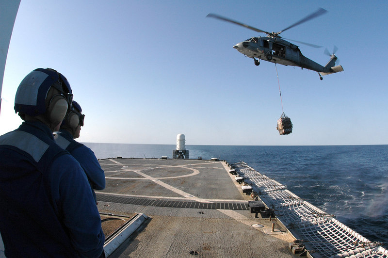ABOARD CGC MIDGETT (Dec. 9, 2006) Crewmembers of the CGC Midgett, homeported in Seattle, Wash., receive supplies from a U.S. Navy helicopter, Dec 9, 2006, while underway in the Gulf of Aden.  Midgett has been deployed since September in support of Operation Enduring Freedom.  U.S. Coast Guard Photo by Petty Officer 2nd Class Mariana O'Leary.