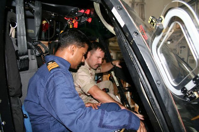 Indian Coast Guard Commander Bose gets some familiarization in the cockpit of the Coast Guard's HH-65C. Aviators from MIDGETT and SAMAR conducted training on each other's embarked aircraft.