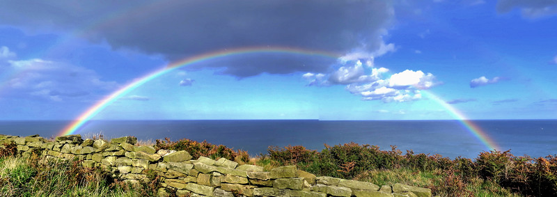 After walking through a caravan site we reached the sea - a short shower produced this double rainbow to welcome us.   Please excuse the jagged horizon - I must have moved a little taking the panorama shot