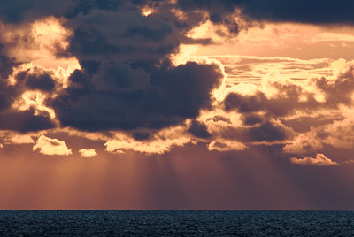 Sunburst clouds storm over ocean