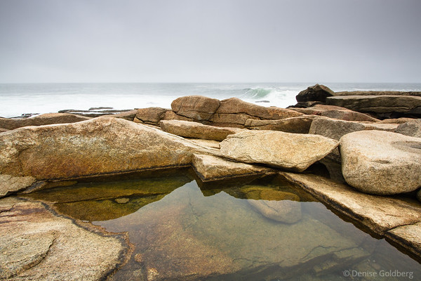 sculpted rocks along the shore capture pools of water