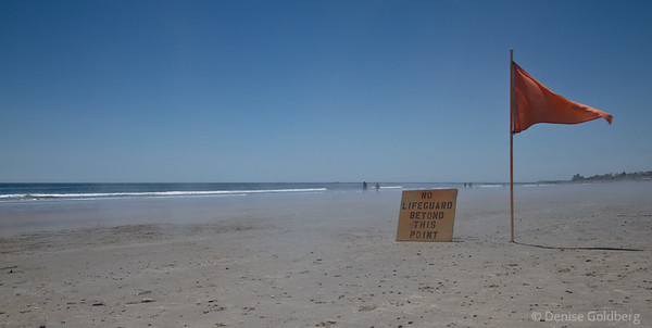 lifeguard warning sign, mist rising from beach sand
