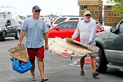 080313 - LANTANA  - Dozens of scuba divers took part in the 3rd Annual Southeast Florida Reef Cleanup, in search of trash that has collected on the natural reefs off the Palm Beach County coast. Pictured at right is Dolphin Sun Dive Charters Captain Bill McKissock carrying garbage to the dumpster with Lake Worth resident Craig Shelanskey.  The trash was removed by a group of divers representing Dolphin Sun Dive Charters, one of the participating dive charters.  Photo by Tim Stepien