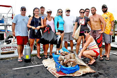 080313 - LANTANA  - Dozens of scuba divers took part in the 3rd Annual Southeast Florida Reef Cleanup, in search of trash that has collected on the natural reefs off the Palm Beach County coast. Pictured are a group of divers representing Dolphin Sun Dive Charters proudly displaying the garbage they removed from the reef and ocean.  Photo by Tim Stepien
