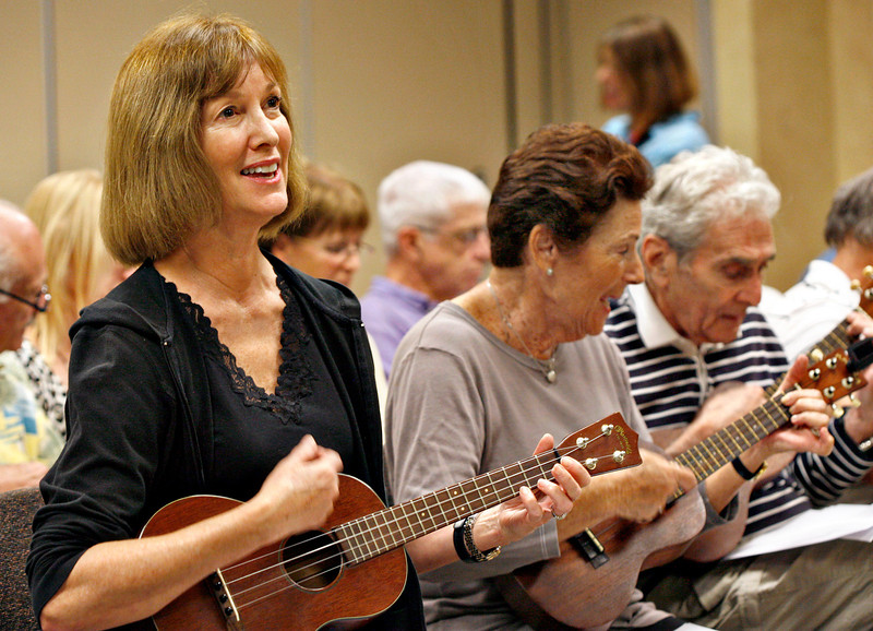 """011414 - DELRAY BEACH  - Tavit Smith, a retired Delray Beach psychotherapist and ukulele player held his first Ukulele Get-Together, for players of all abilities on Jan. 14 at the Delray Beach Public Library. Pictured left is Delray/Ohio resident Barbara Davis, a student of Tavit Smith singing and playing her ukulele during the Delray Beach Public Library  """"Ukulele Get-Together"""".  Photo by Tim Stepien/The Coastal Star"""